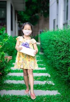 Litte menina asiática usando máscara em vestido amarelo segurando uma caixa de presente em seu aniversário no parque