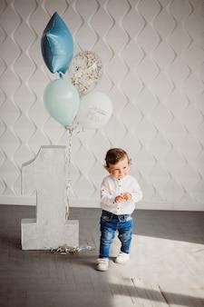 Little boy brilha com balões azuis befoe grande número um em um quarto aconchegante
