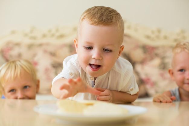 Little boy fazendo o braço longo para o biscoito