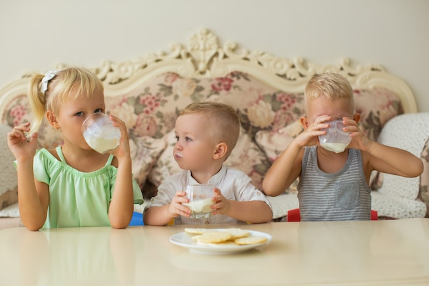 Little boys and girl drinking milk at table