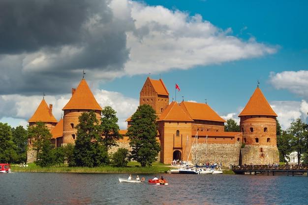 Lituânia. vista no castelo trakai através do lago e o iate branco à vela.