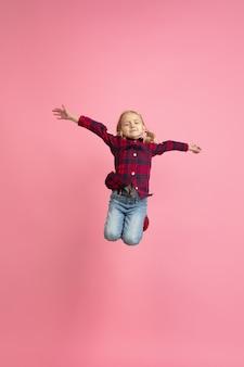 Livre e feliz, voando, pulando alto. retrato da menina caucasiana na parede rosa. bela modelo com cabelo loiro. conceito de emoções humanas, expressão facial, vendas, anúncio, juventude, infância.