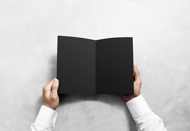 Livreto de brochura preto em branco aberto à mão