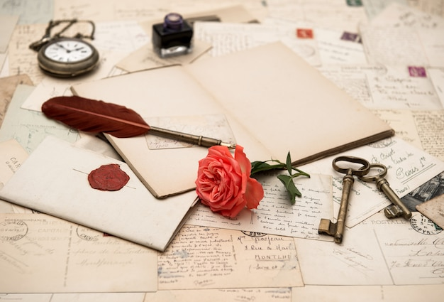 Livro aberto, acessórios antigos e cartões postais