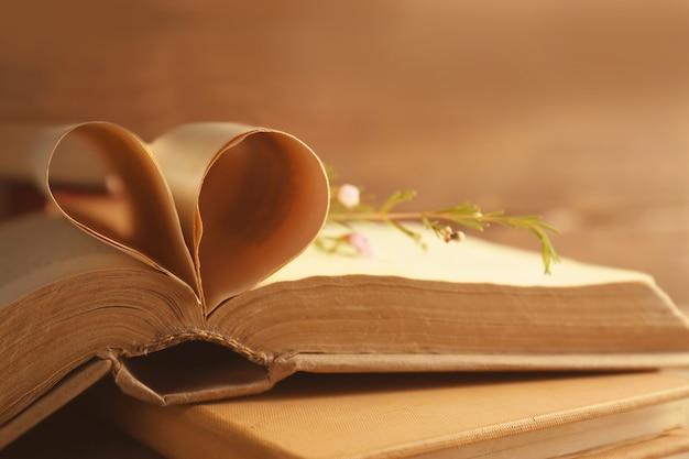 Livro aberto antigo com coração feito de páginas na superfície desfocada