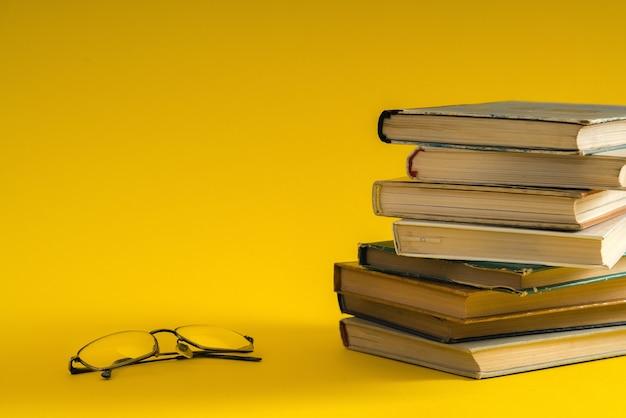 Livro aberto, capa dura, livros coloridos e óculos de leitura nas laterais.