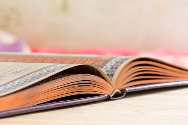 Livro aberto com borda dourada em cima da mesa