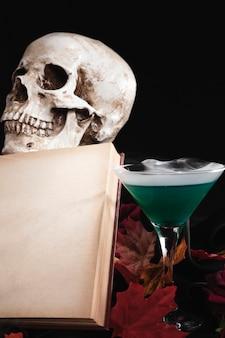 Livro aberto com caveira e bebida