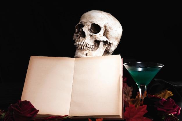 Livro aberto com crânio humano e bebida