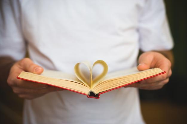 Livro aberto com folhas em formato de coração nas mãos masculinas