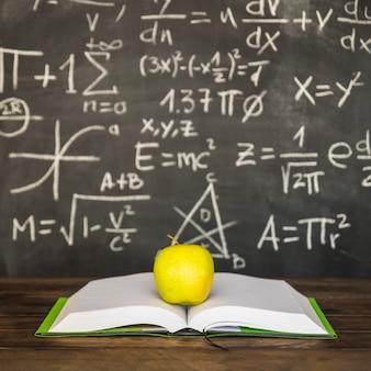 Livro aberto com maçã na mesa perto de lousa