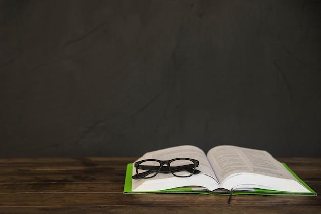 Livro aberto com óculos na mesa