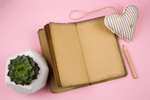 Livro aberto com papel antigo, brinquedo macio em forma de coração, lápis e suculenta