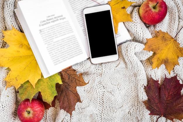 Livro aberto com telefone e maçã ao lado