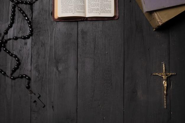 Livro aberto da bíblia e crucifixo na mesa escura, vista superior. imagem plana leiga do novo testamento, cruz e rosário na superfície preta velha