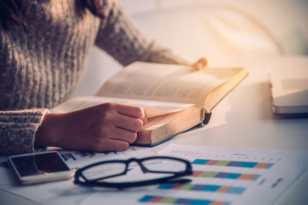 Livro aberto da mão do foco para ler no trabalho de mesa com iluminação do ouro na manhã