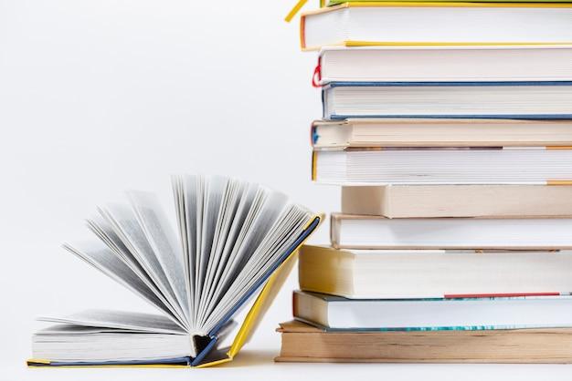 Livro aberto de cópia-espaço ao lado da pilha de livros