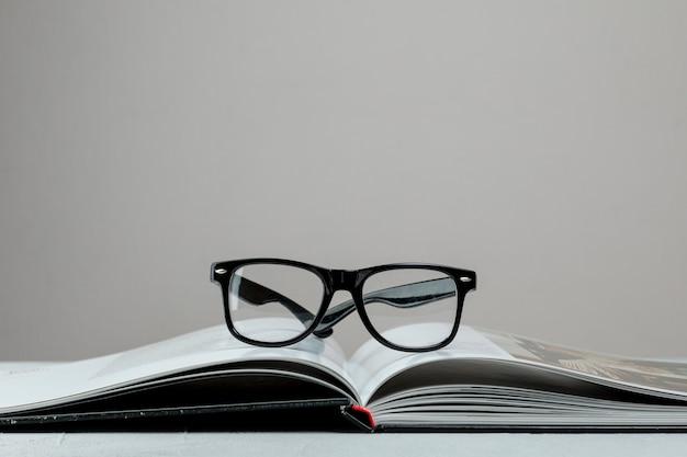 Livro aberto de vista frontal com óculos