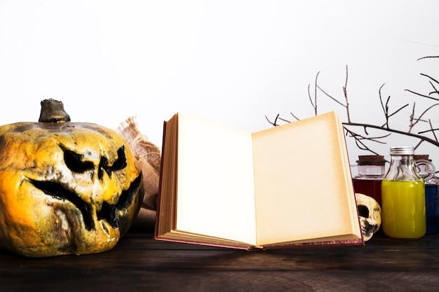 Livro aberto e abóbora assustadora na mesa