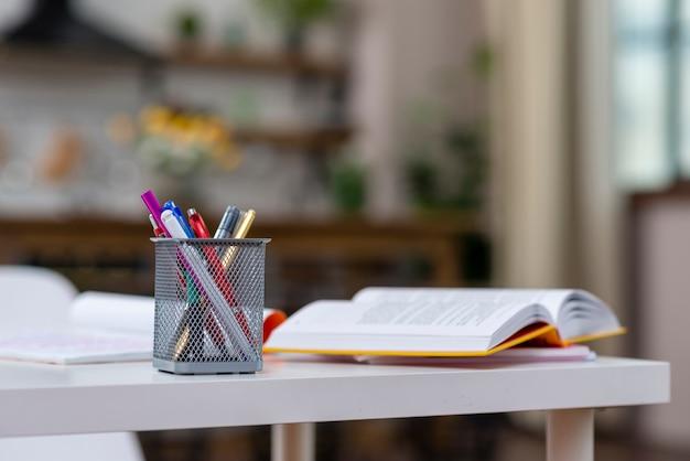 Livro aberto e canetas em cima da mesa