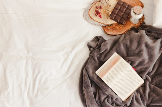 Livro aberto e cobertor perto de barra de chocolate
