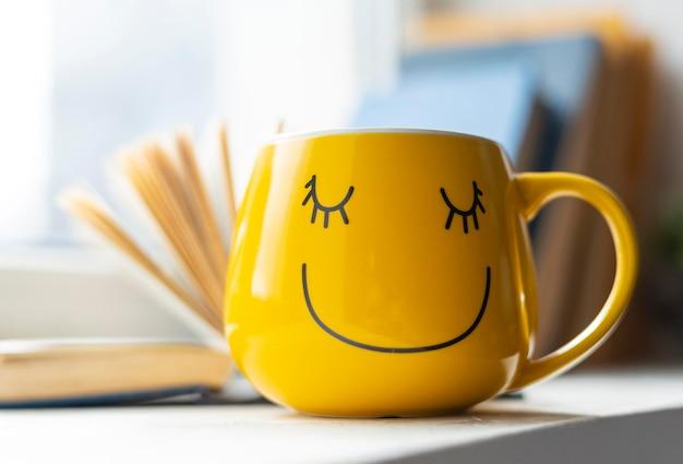 Livro aberto e copo amarelo sorridente