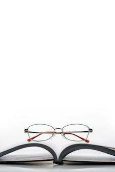 Livro aberto e óculos isolados em uma parede branca com espaço para texto.
