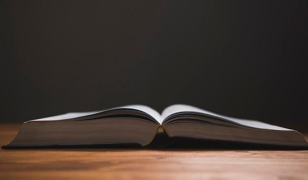 Livro aberto em uma mesa de madeira em uma superfície escura