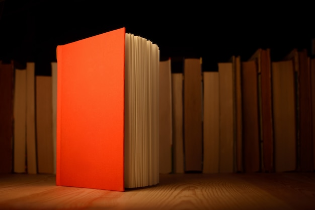 Livro aberto em vermelho fica na mesa de madeira na frente da fileira de outros livros