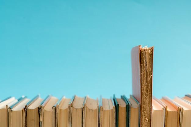 Livro aberto, livros coloridos de capa dura em cima da mesa. de volta à escola. copie o espaço para o texto. educação, estudo, aprendizagem, conceito de negócio