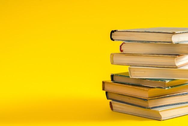 Livro aberto, livros coloridos de capa dura empilhados sobre a mesa.