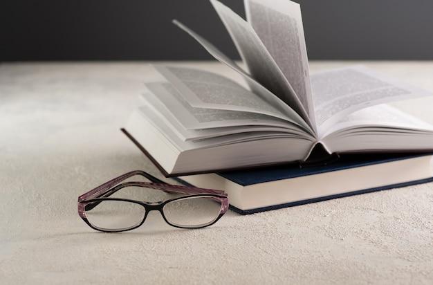 Livro aberto na mesa com óculos de leitura