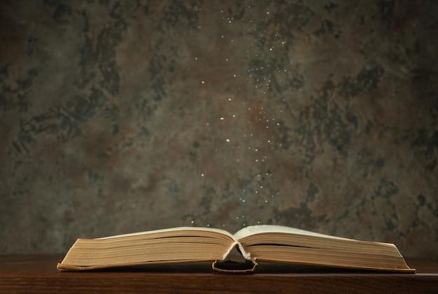 Livro aberto na mesa com poeira