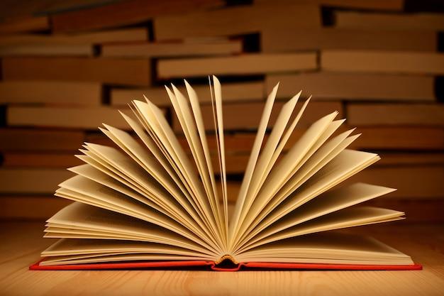 Livro aberto na mesa de madeira com uma parede de livros na parede