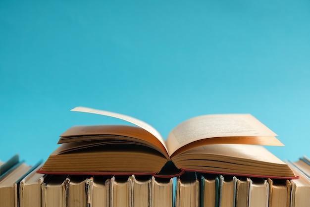 Livro aberto na superfície azul, livros de capa dura na mesa de madeira.