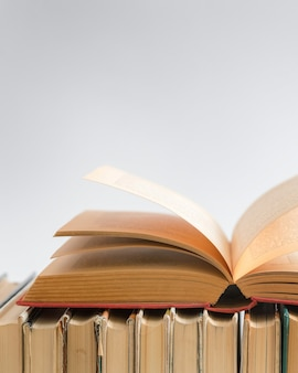 Livro aberto na superfície branca, livros de capa dura na mesa de madeira.