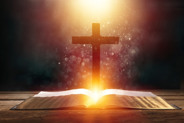 Livro aberto na velha mesa de madeira com cruz