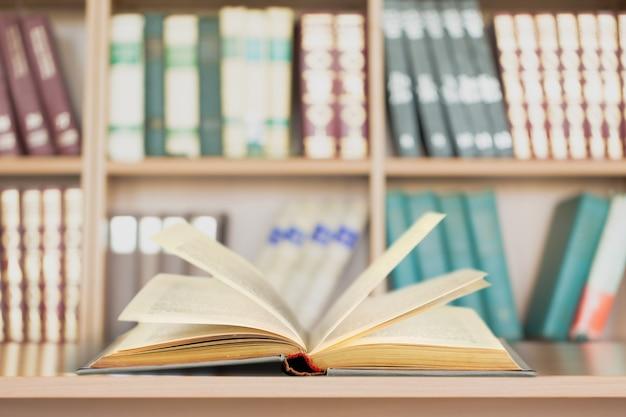 Livro aberto na velha mesa de madeira.