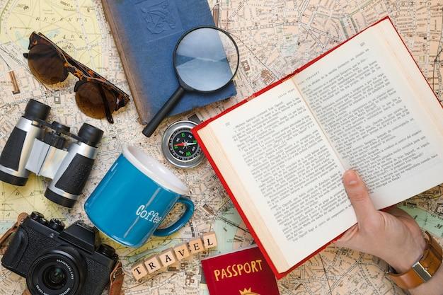 Livro aberto rodeado por elementos de viagem