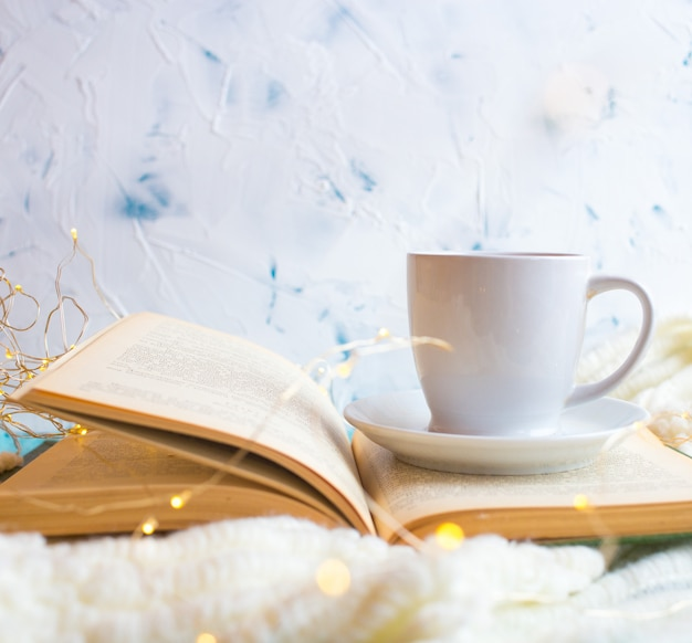 Livro aberto sobre a mesa com luzes e xícara de café