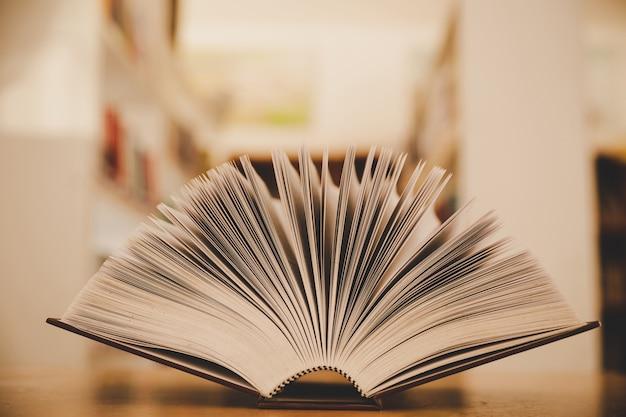 Livro aberto sobre a mesa e a ilha de estantes no fundo de sala de aula de estudo escola