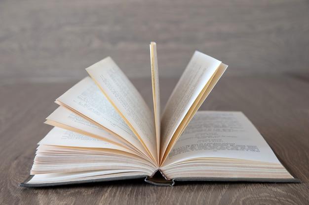 Livro aberto sobre fundo de madeira