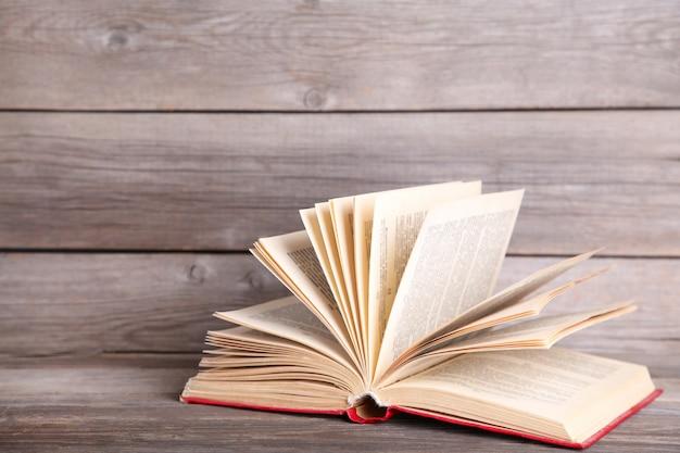 Livro aberto sobre uma mesa de madeira cinza
