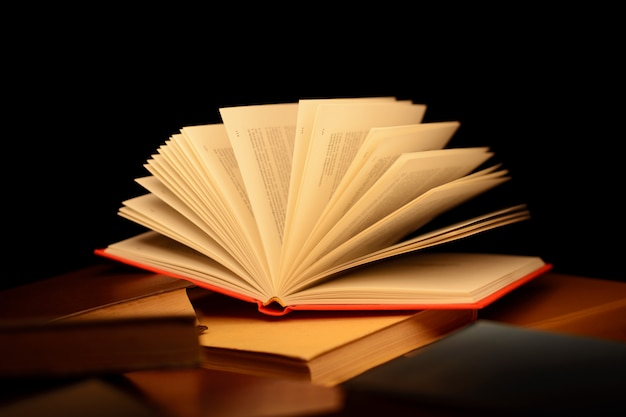 Livro aberto vermelho em cima da mesa com muitos outros livros fechados