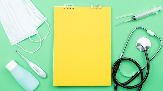Livro amarelo em branco com equipamentos médicos e equipamentos de prevenção de vírus covid-19.