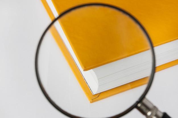Livro amarelo fechado com uma lupa.
