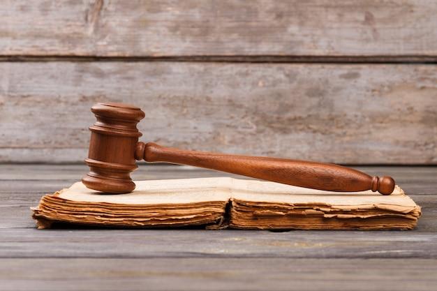 Livro antigo antigo e martelo de madeira. conceito de lei e justiça.