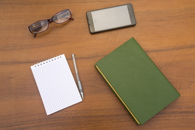 Livro antigo, bloco de notas, caneta, óculos e smartphone na mesa de madeira