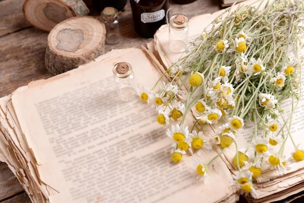 Livro antigo com flores secas e garrafas na mesa close-up