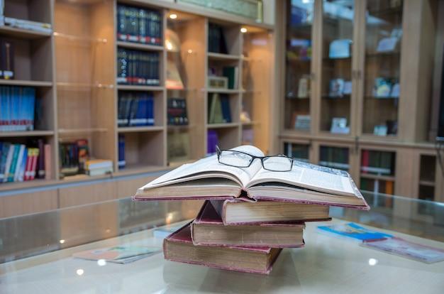 Livro antigo com óculos na mesa de vidro na biblioteca